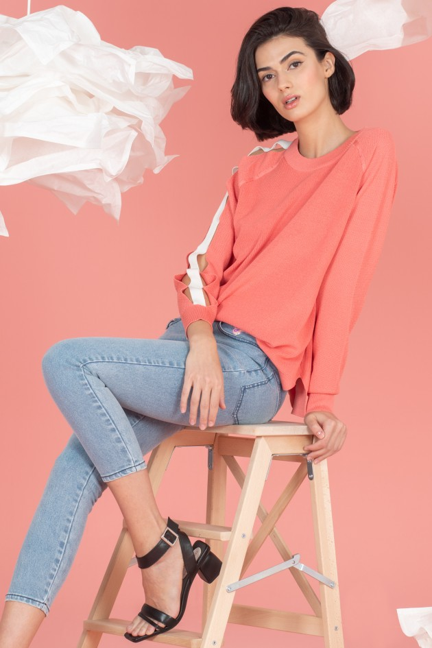 Knit sweater with perforated sleeves